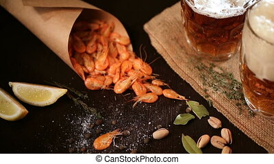 Fills the glass of Beer mug and grilled shrimps on wooden...