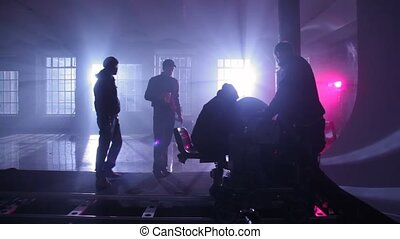 film crew adjusts equipment on rail cart in dark room shined...