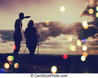Film effect. Couple enjoying marvellous moments during sunset . Young pair of hikers on the peak