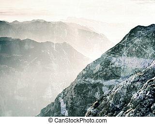Film grain effect.  Fantastic dreamy sunrise, sharp contour of mountain above mist.