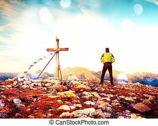 Film grain effect. Man walk along the cross at mountain peak built to Alps victiims.