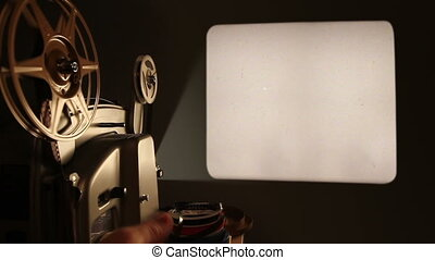 An antique 8mm film projector is turned on in a dark room, and projects a blank movie with a dust and hair texture, lifted from real 8mm film. Includes projector audio.