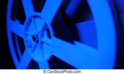 Film projector with dramatic blue lighting and selective focus. Retro film production still life. Concept of film-making. Old 8mm projector is turning off. Close-up of a reel with a film