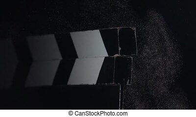 Film slate being clapped . Close up. Black background. Slow motion