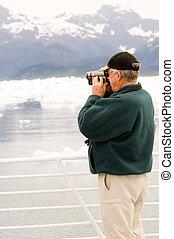Filming Alaska - Senior citizen with videocamera at Alaskan ...