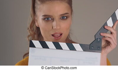 Filming. Close up of Beautiful young woman with clapperboard in hands