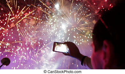 Filming fireworks - Man filming colorful fireworks on his...
