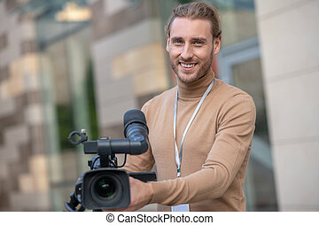 Filming process. Smiling fair-haired cameraman standing behind camera, posing