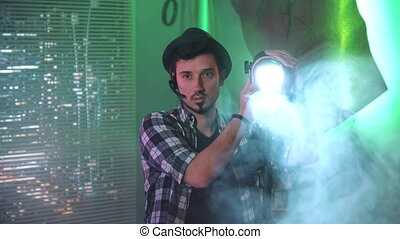 Medium shot of filmmaker looking at camera while using a Fresnel lamp. There is green background.