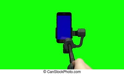Filmmaker's hand is lifting up steadicam gimbal stabilizer with blue screen on smartphone. Professional equipment for videographer for making high quality video. Close-up motion on green background.