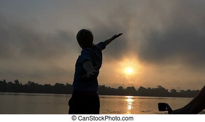 Filmming of Young Man Stands on a River Bank, Raises His Fists at Sunset