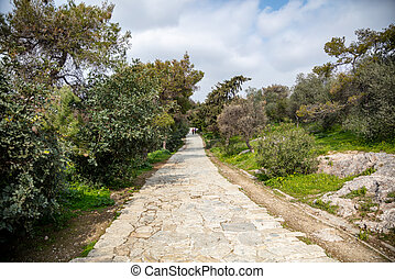 Filopappou hill, Athens, Greece. Paved path under ancient Greek Acropolis rock, between trees of Philopappos forest background. Day, blue cloudy sky, people on way.