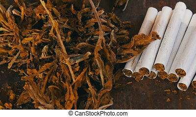 Filter homemade cigarettes or roll-up next to dry tobacco...