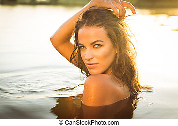 filtered closeup image of beautiful brunette young woman with naked shoulders swimming in water at sunset outdoors copy space background