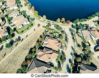 Filtered image aerial view new lakeside suburban house with bright autumn orange color near Dallas
