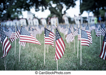 Filtered image lawn American flags with blurry row of people carry fallen soldiers banners parade