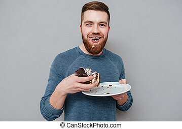 Filthy bearded young man eating cream cake