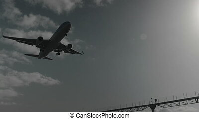 Slow motion shot of passenger airliner descending for approach, bottom view with sun shining in the sky