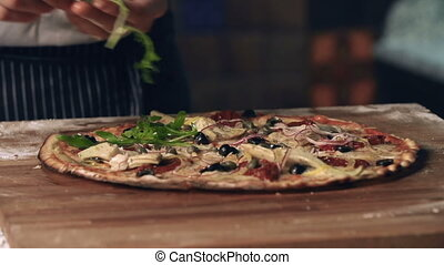 Final Flourish - Close up of basil adding to pizza as a...