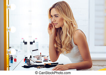 Final touches. Side view of beautiful young woman using cotton disk and looking at her reflection in mirror while sitting at the dressing table
