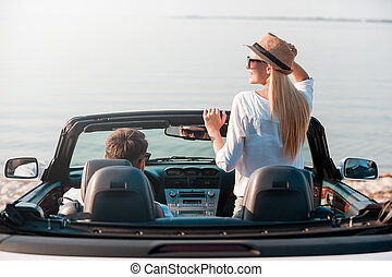 Finally arrived! Rear view of smiling young woman enjoying scenery while her boyfriend sitting near on front seat of their convertible