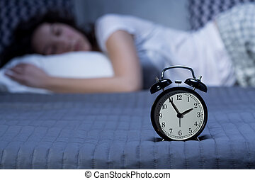 Close-up of a black, vintage alarm clock on a bed where a young woman is lying in the blurry background