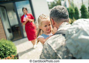 Military man coming back home and seeing his wife and daughter