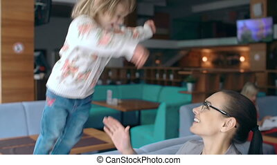 Tilt down the girl jumping to the arms of her mother