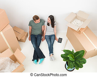happy young couple lying on floor with boxes around them. moving house