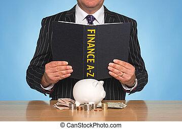 A businessman sat at a desk reading a FINANCE A-Z book