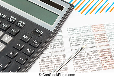 Finance. Black calculator on financial graphs on desk