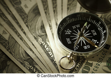 concept with dollars and compass, selective focus on nearest part of arrow