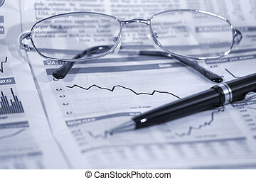 Glasses and pen on financial statistics