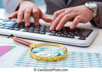 Finance professional working on keyboard with reports