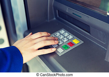 close up of hand entering pin code at cash machine -...