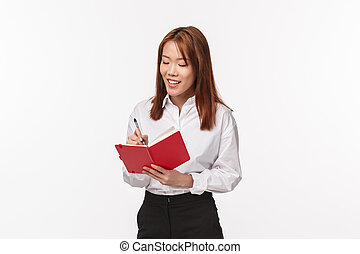 Finance, women and business concept. Successful young asian office lady working over project, writing in notebook, look at diary with pleased smile, creating schedule, standing white background