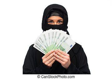 muslim woman in hijab with money over white - finances and...