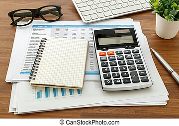 Financial accounting with calculator and notebook