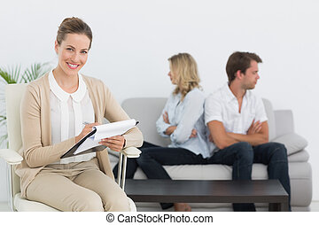 Financial adviser writing notes with couple in background -...