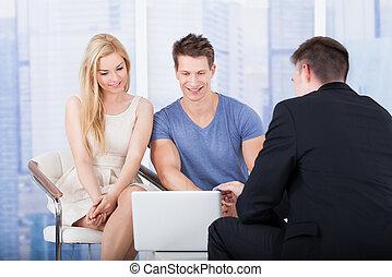 Financial Advisor Explaining Investment Plan To Couple On...
