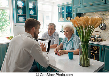 Financial advisor talks with elderly clients in their home