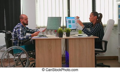 Businesswoman analysing financial statistics talking with handicapped coworker sitting in wheelchair checking graphs on desk in building office. Disabled businessman using modern technology