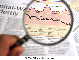 Hand holding a magnifying glass focusing on a chart in the business section of the newspaper.