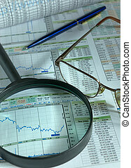 financial analysis - Magnifier and glasses atop of the...