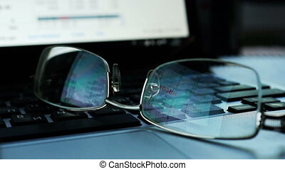 Glasses on a keyboard of laptop with Share prices and quotes...