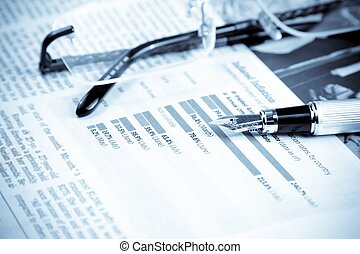 financial chart and graph near pen and glasses