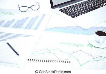 Financial charts on the desktop and a cup of coffee