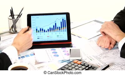 Financial charts on the table, developing a business project and analyzing market data information, tablet in business negotiations, graphics