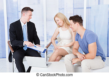 Financial Consultant Presenting New Project Investment To Couple