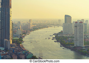 Financial district and Chao Phraya River at sunset in Bangkok city, Thailand